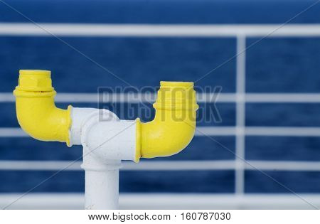Nautical equipment of the ferry boat deck - yellow pipe and white railing on the background