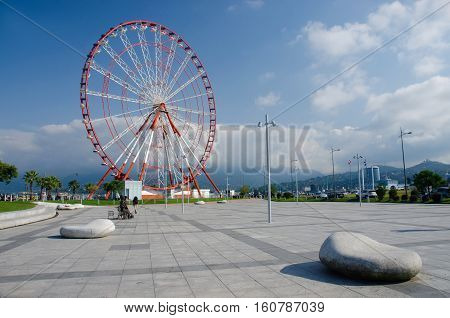 Ferris wheel on the Batumi seafront with Caucasus mountains on the background blue sky and stone-shaped benches,Georgia,Adzharia