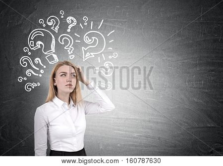 Blond woman in shirt is scratching her head while standing near a blackboard with question marks. Mock up