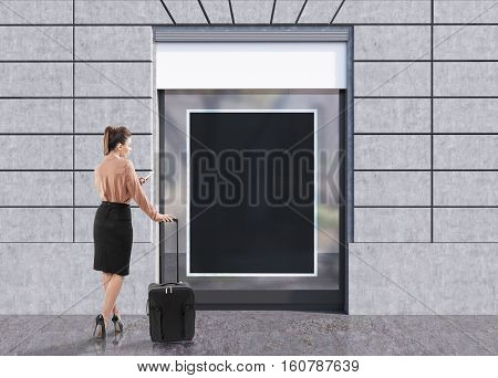 Rear view of a woman in a brown blouse with a luggage standing near a blank shop window. Mock up. Concept of travelling