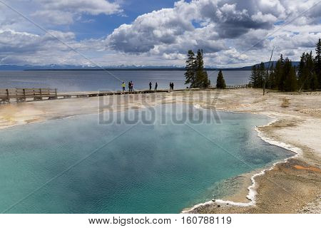Yellowstone United States - May 31 2015: Clear aqua hot spring with deep central hole steam and limy shoreline people on boardwalk West Thumb area of Yellowstone National Park Wyoming.