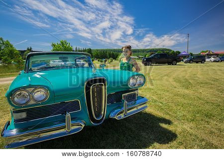 Milton, Ontario, Canada, June 18, 2016, Nice front view of old vintage classic car with pretty smiled little girl standing beside