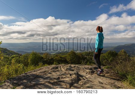 Woman has this inspirational view across the valleys and mountains below in the Shenandoah National Park