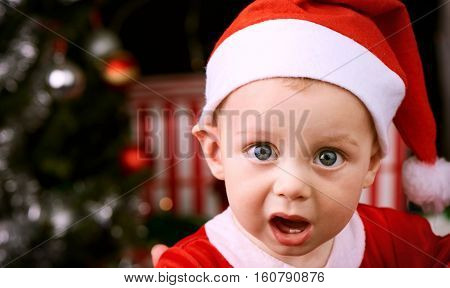 9 month old baby boy with shocked expression looking into the camera wearing a Santa Claus outfit for the christmas festive season.