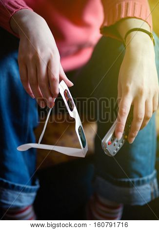 Women hand holding a remote control in one hand and anaglyph eyeglasses in other hand. Useful file for illustration additction to multimedia.