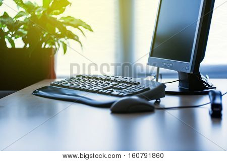 Personal computer on a desk in bright modern office lit by yellow sun coming from the window