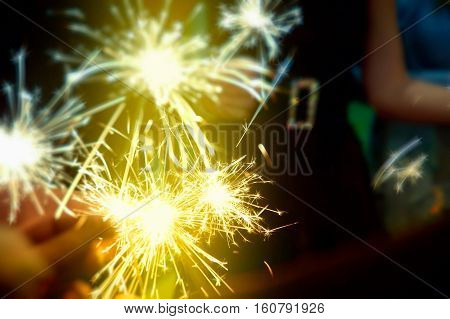 Sparkler in hands on a party - great celebration of Christmas New Year birthday easter wedding and other important anniversaries