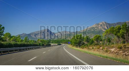 Sunshine on Coastal highway.  Lone white car drives along through foothills and mountain ranges on the edges of continental Europe in Spain.
