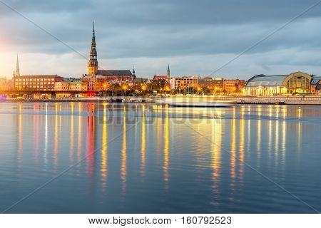 Night view on the illuminated riverside with reflection on the river in Riga, Latvia