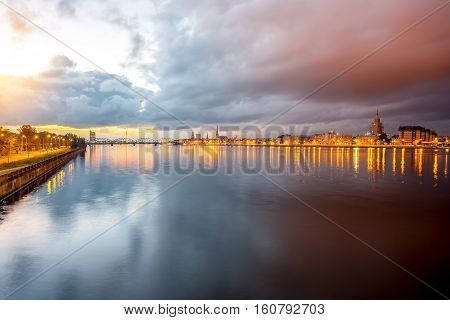 Night view on the illuminated bridge with reflection on the water in Riga, Latvia. Wide angle view with copy space