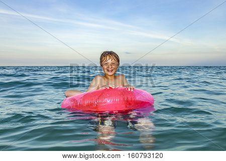 boy in a swim ring has fun in the ocean