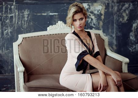 Fashion model with blond hair. Young attractive woman, siting on the sofa