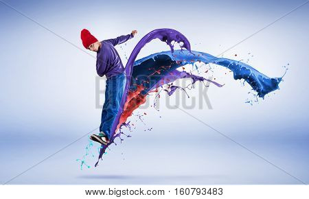 Young male dancer in jump on white background with colorful paint plashes