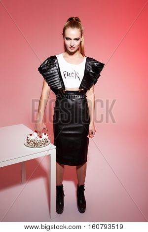 Young beautiful brutal blonde girl in black leather skirt push hand in cake over pink background.