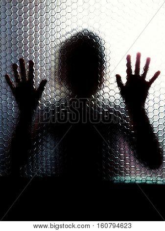 Scared child behind glass door showing hands