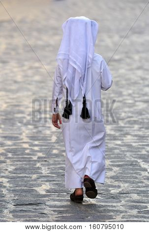 Figure of unidentifiable Arabic boy in white thobe walking away in Doha, Qatar.