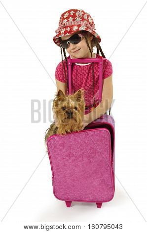 Little fashionable girl with her small yorkie and small pink suitcase