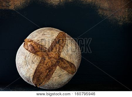 Homemade rye artisan sourdough bread over dark background copy space