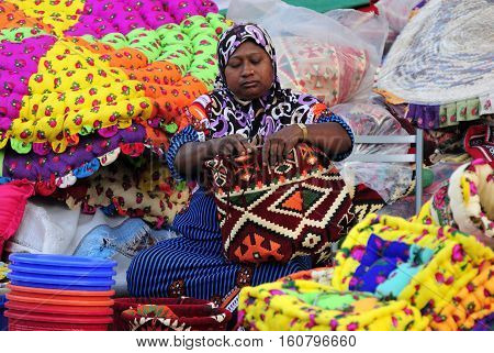 Doha, Qatar - November 10, 2016. Female trader weaving a bag at Souq Waqif market in Doha, with multicolour bags, kilims and other items.