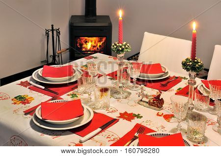 Beautiful new year table with red napkin and Cutlery on a background of room with fireplace