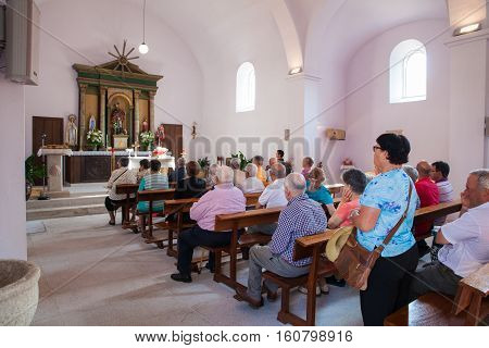 MELIDE SPAIN - AUGUST 14: People during mass in San Pedro catholic Church on August 14 2016