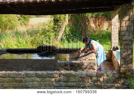 MELIDE SPAIN - AUGUST 14: A woman washes her clothes in the wash house on August 14 2016
