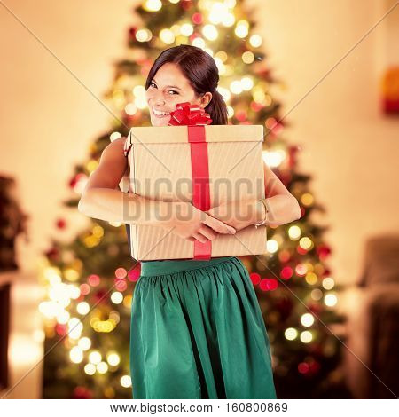 Happy woman receives a big xmas gift and on background lights of the Christmas tree