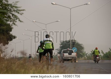 pair of asian cyclists a man and woman riding on road in Golden triangle in triahlon sports competitions Chiang rai Thailand.