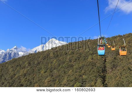 Lijiang, China - November 11, 2016: Cable Car On Foreground With Some Tourists Inside And Jade Drago