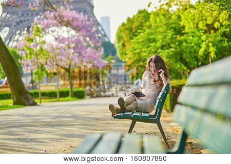 Beautiful Young Woman In Paris Reading On The Bench