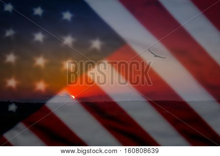 Old American flag background for Memorial Day or 4th of July, eagle and sunset in a scenic foreground and blurred out flag in the backdrop