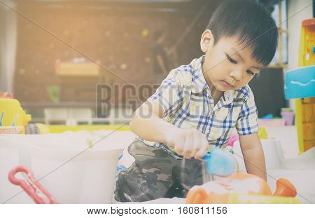 Japanese boy is playing in educational sandbox.
