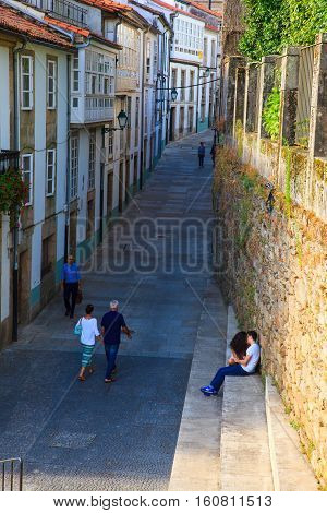 SANTIAGO SPAIN - AUGUST 17: Couple of teen lovers sitting on staircase on August 17 2016
