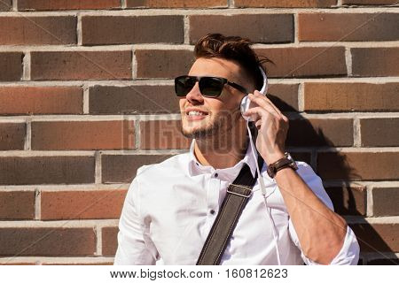 music, technology and people concept - happy smiling young man in headphones and sunglasses over brickwall
