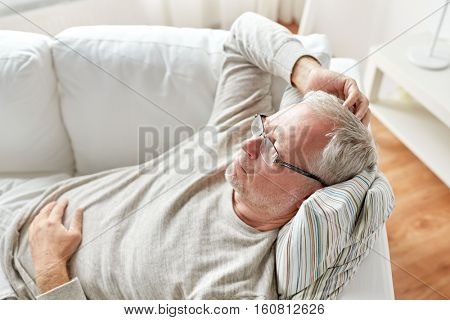 old age, problem and people concept - close up of senior man in glasses lying on sofa and thinking at home