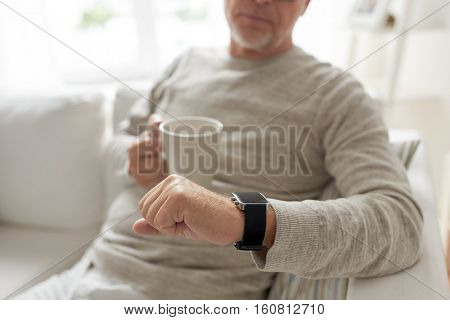 time, morning and people concept - close up of senior man with coffee or tea mug looking at wristwatch at home