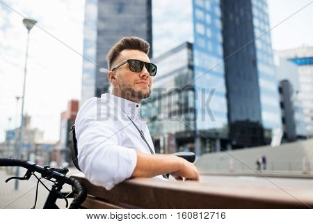 people, style, leisure and lifestyle - happy smiling young man with bicycle sitting on city bench
