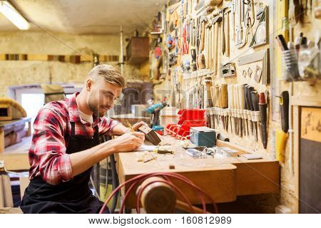 profession, carpentry, woodwork and people concept - carpenter with wood plank and notebook working at workshop