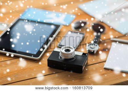 travel, tourism, winter holidays and technology concept - retro film camera, gadgets and personal stuff over snow