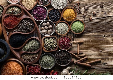 Set of colorful spices in different bowls on wooden table. Top view.