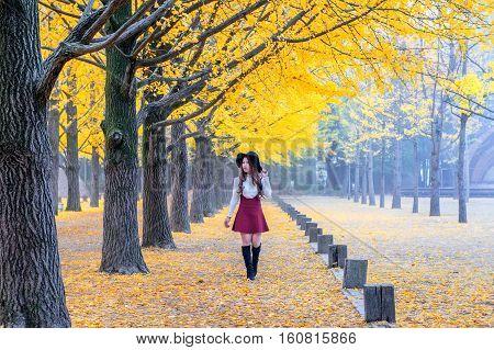 Beautiful Girl with Yellow Leaves in Nami Island Korea.