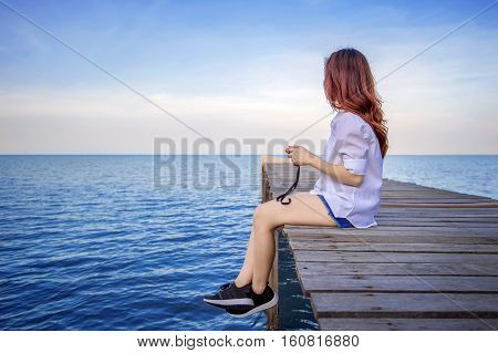 Girl sitting alone on a the wooden bridge on the sea. Vintage tone style.