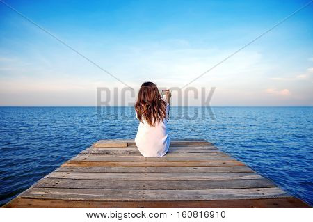 Girl sitting alone and hand holding camera on a the wooden bridge on the sea.