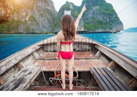 Sexy girl wearing a red bikini in a happy mood on long boat. Lady on boat raises hand. Phi Phi island.
