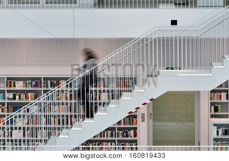 Stuttgart, Germany - April 16, 2015: Interior of modern library in Stuttgart. White staircase with moving person on the background of shelves with books.