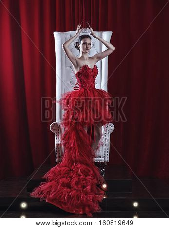 girl in a red dress and a crown on the throne