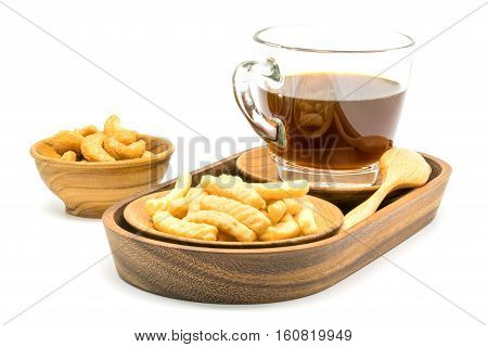 Prawn cracker and a cup of black coffee in a wooden tray with salty cashew nuts in a wooden bowl on white background