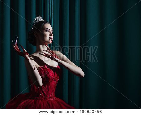 vamp girl in a red dress on the green background