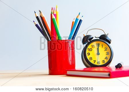 Focus on the clock on white background laid colored pencils and diary memoirs on the wooden floor.