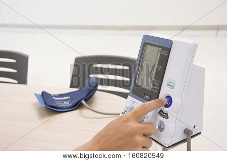 finger push button start on blood pressure digital machine and cuff on the desk